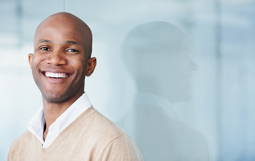 Bald man smiling about his dental care from Dr. Julie Phillips Prosthodontics in Greensboro, NC