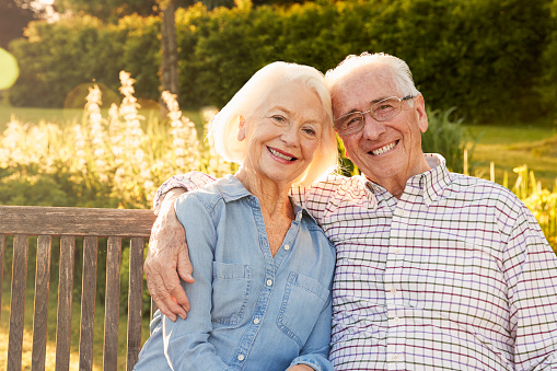 Portrait of a happily married mature couple hugging at a park bench