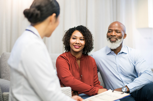 Older Black couple speaking with Dentist about dental implants for them at Dr. Julie Phillips Prosthodontics in Greensboro, NC