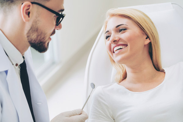 Woman smiling while prosthodontist talks at Julie A. Phillips, DDS, MS