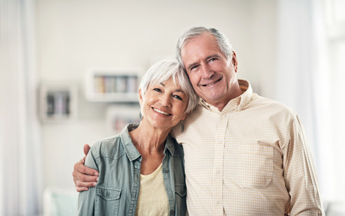 Elderly man and woman smiling about their dental care at Dr. Julie Phillips Prosthodontics in Greensboro, NC